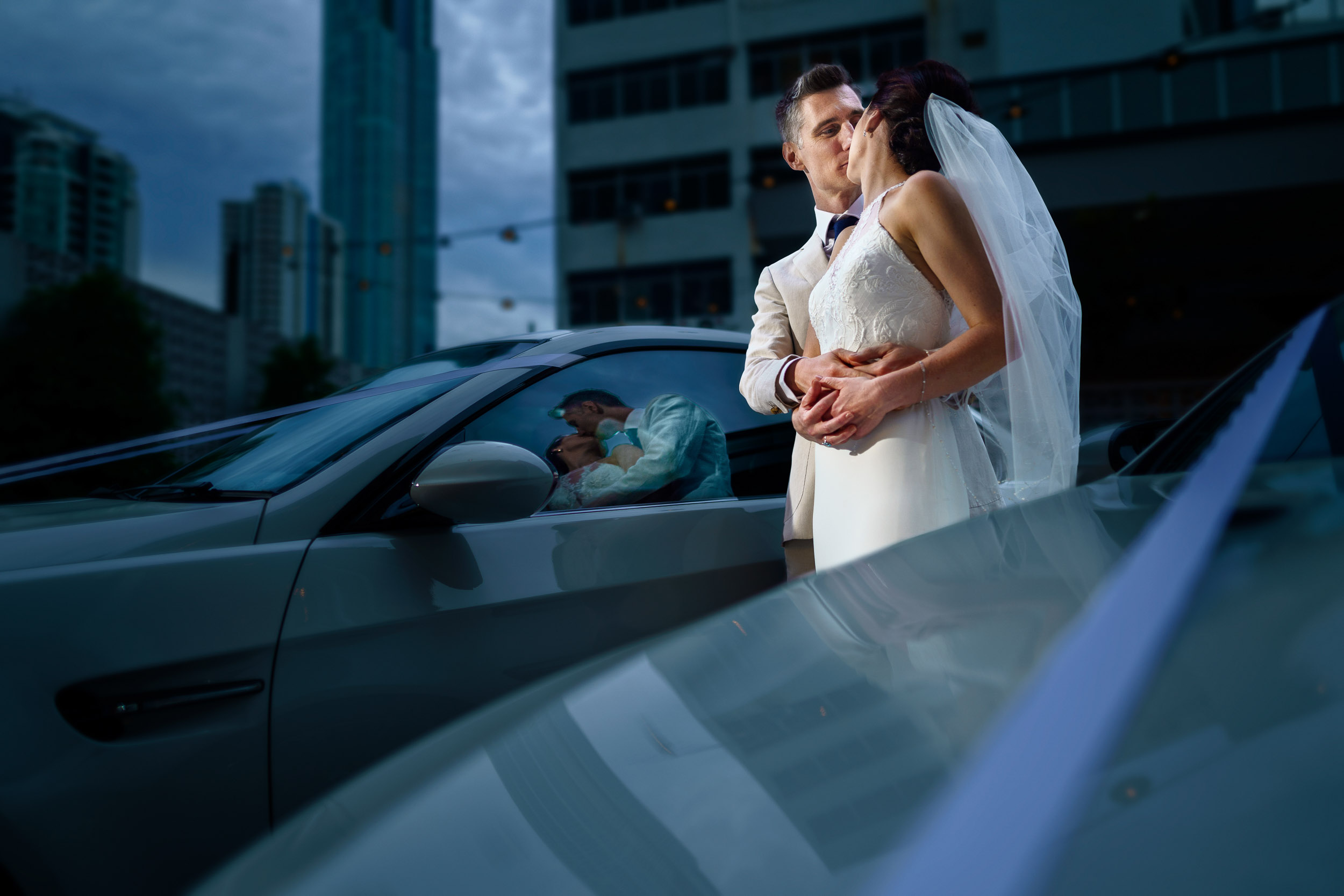 Wedding day portrait of bride and groom with BMW cars.